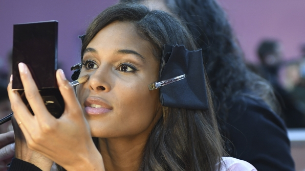 French model Cindy Bruna watches as a makeup artist applies some highlighter.