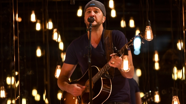 Co-host Luke Bryan rocks a backwards cap as he strums his acoustic guitar.