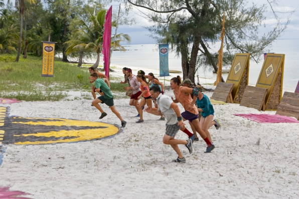 The castaways sprint toward the obstacle course.