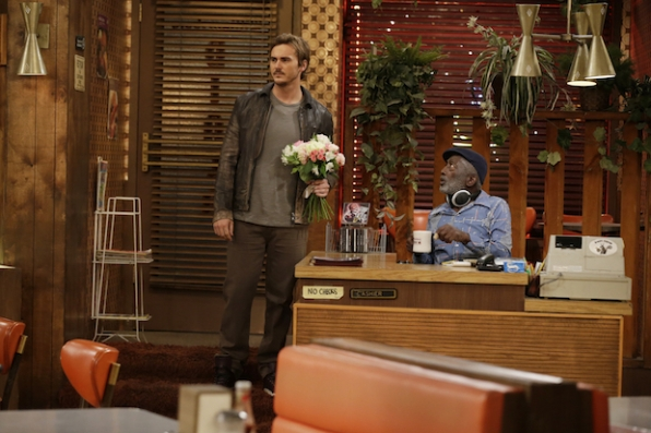 Max's date shows up to the diner with flowers.