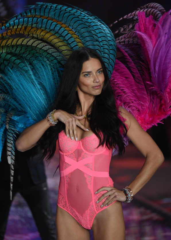 Adriana Lima is proud as a peacock in a pink one-piece and giant feathered wings