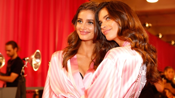 Taylor Hill and Sara Sampio rock pink satin robes before donning their wings