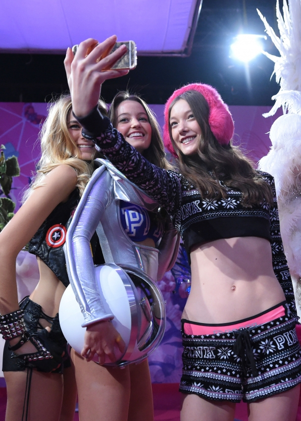 Megan Puleri and Yumi Lambert pose for a group selfie backstage