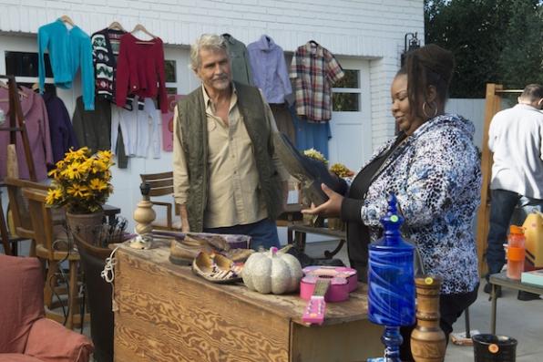 John greets a customer at the yard sale.