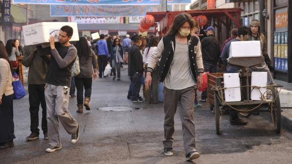 An UnSub walks down a busy Japanese street.