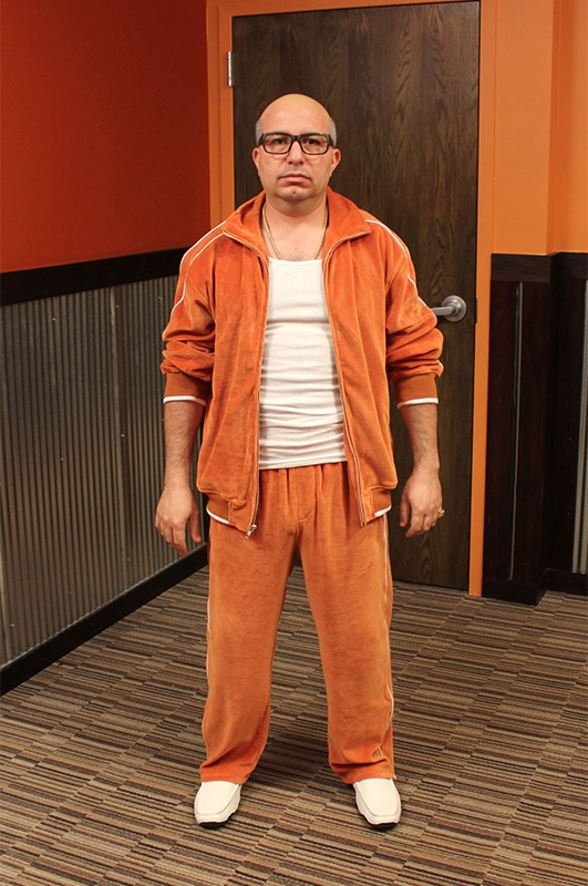Nader rocks a head-to-toe orange velour sweatsuit when he goes undercover.