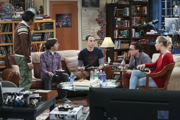 Sheldon grabs a plate while his friends sit down for dinner.