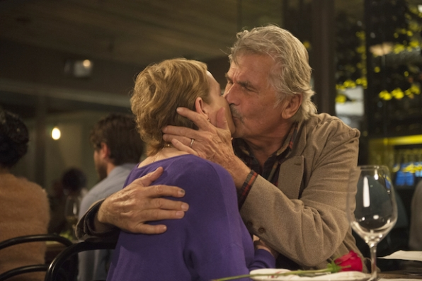 John and Joan share a steamy kiss at dinner.