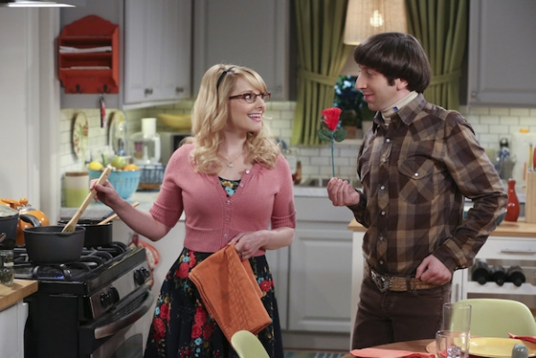 Howard gives Bernadette a rose in the kitchen.