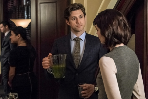 Gareth offers Laurel a drink.