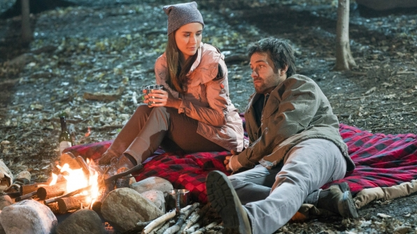 Christina and Garrett sit by the campfire.