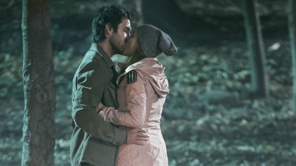 Garrett and Christina kiss in the woods.