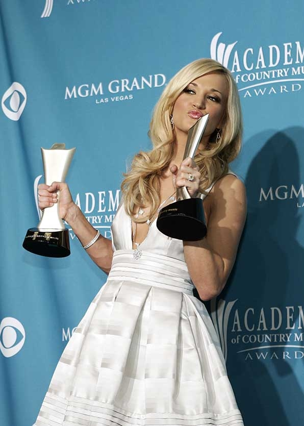"Carrie Underwood matched her ""Entertainer Of The Year"" and ""Triple Crown"" statues on the red carpet at the 45th Annual Academy of Country Music Awards."