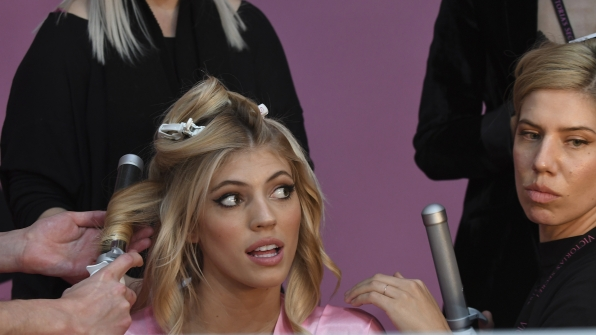 American model Devon Windsor is surrounded by a bevy of hairstylists.
