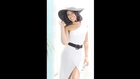 Karla Mosley offers a big smile under a floppy straw hat.