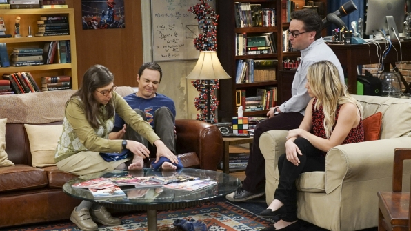 The group takes a closer look at the damage to Sheldon's foot.