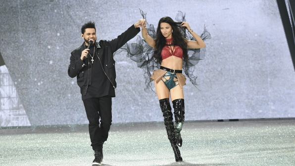 The Weeknd gives Angel Adriana Lima a hand down the runway.