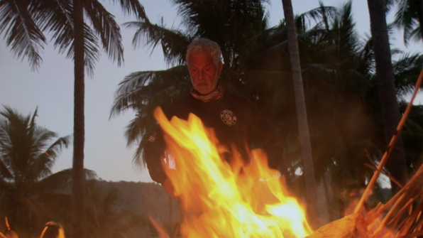 As day turns to night, Joe keeps an eye on the tribe's fire.
