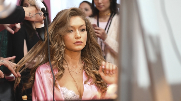 Gigi Hadid puts on finishing touches before she struts the runway.