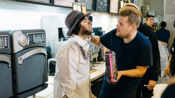 James gently applies a healthy dose of ground coffee to Jason's face.