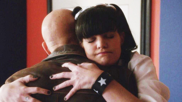 Abby's face scrunches up as she hugs Fornell.