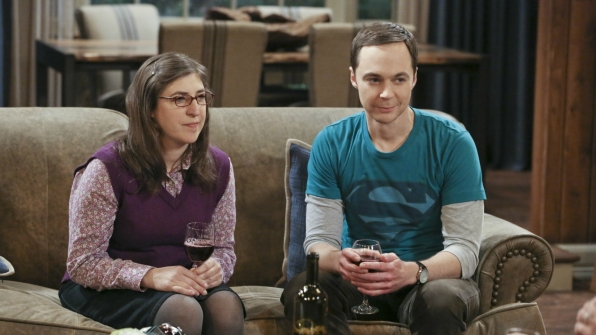 Amy and Sheldon listen closely to the rules of a drinking game.