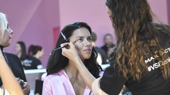 Angel Adriana Lima sits for makeup and hair.
