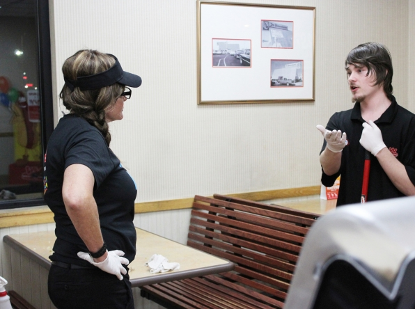 Cynthia does some cleaning while talking with one of Wienerschnitzel's night managers.