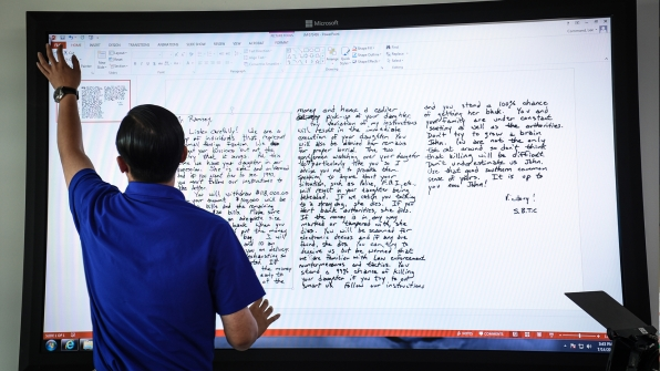 A lab technician prepares an in-depth examination of the ransom note.