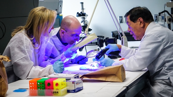 Jim Clemente and Laura Richards look under the microscope in Dr. Henry Lee's Connecticut crime lab.