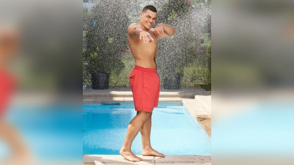 Josh Martinez mugs for the camera in siren-red swim trunks.