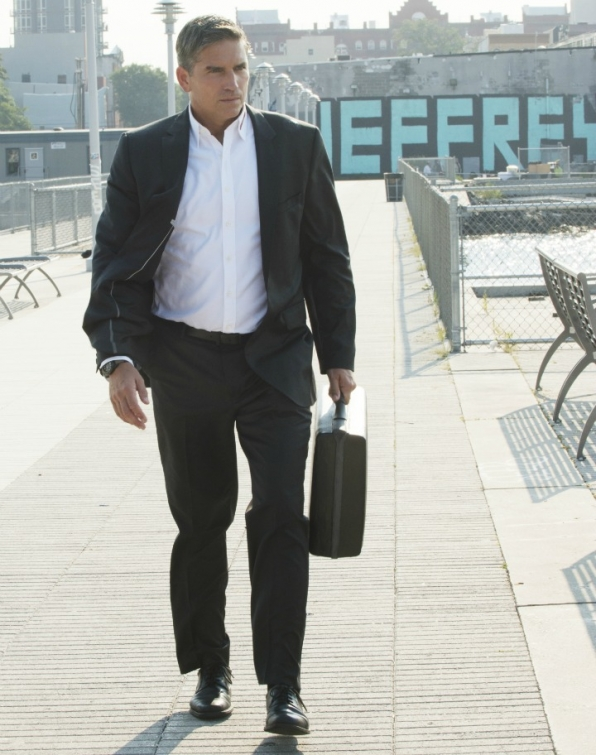 Reese carries the briefcase close by his side.