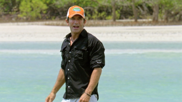 Host Jeff Probst cheers on the castaways from the sidelines.