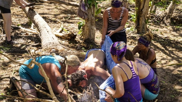 The members of Takali put their heads together to spark a fire.