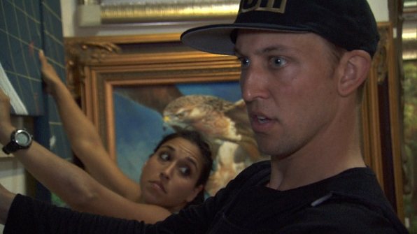 Dana and Matt try to stay focused as they hang their crop of paintings.