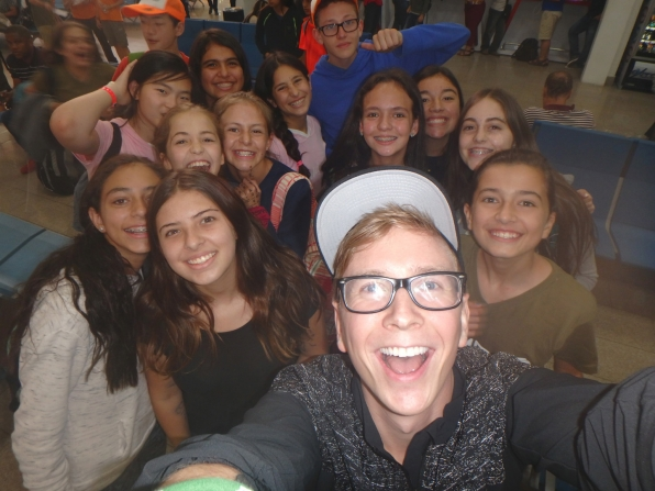 Tyler poses with a gaggle of fans in the airport for the ultimate selfie.