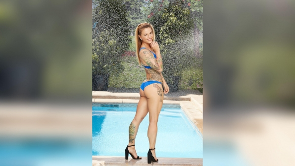 Christmas Abbott shows off her body art in a skimpy blue bikini.