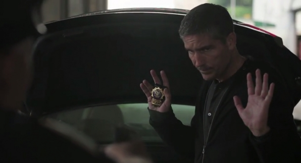 Reese flashes his badge while pretending to be a cop.